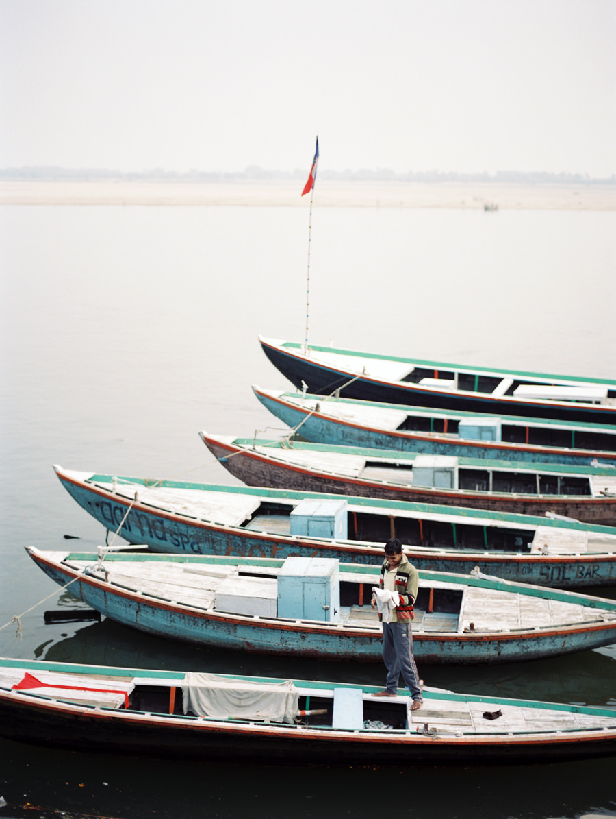 Man stands on boats along the Ganges in Varanasi