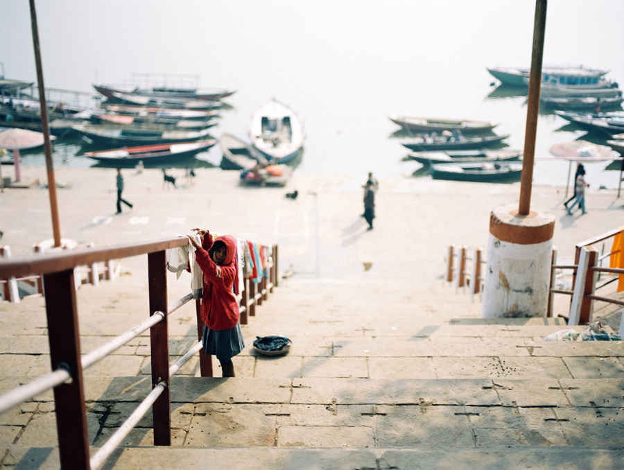 Young child hangs clothes on the steps of the Ganges